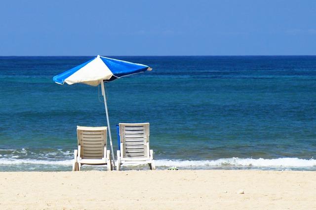 Two Deckchairs Under an Umbrella at the Beach