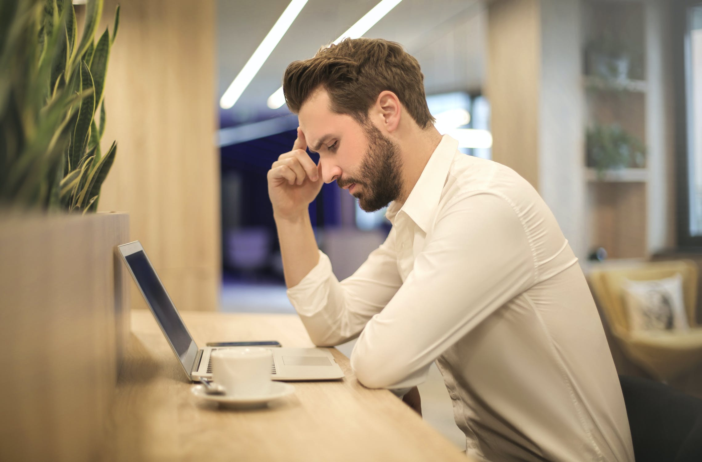 Individual stressed working over laptop due to unfair prejudice claims.